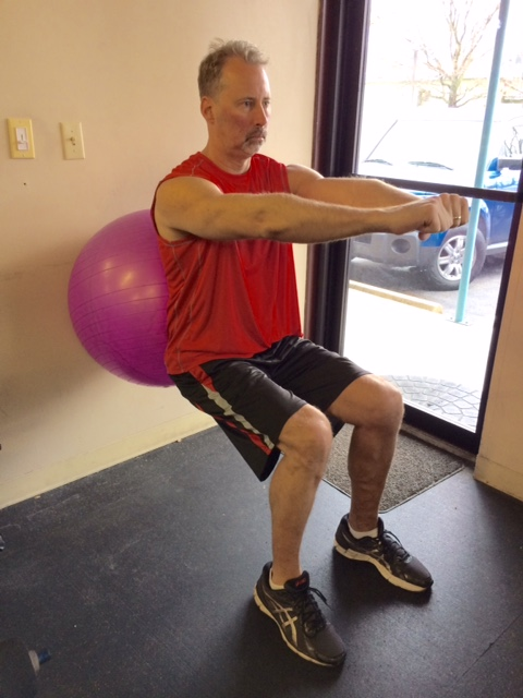wall sits with ball for office exercise